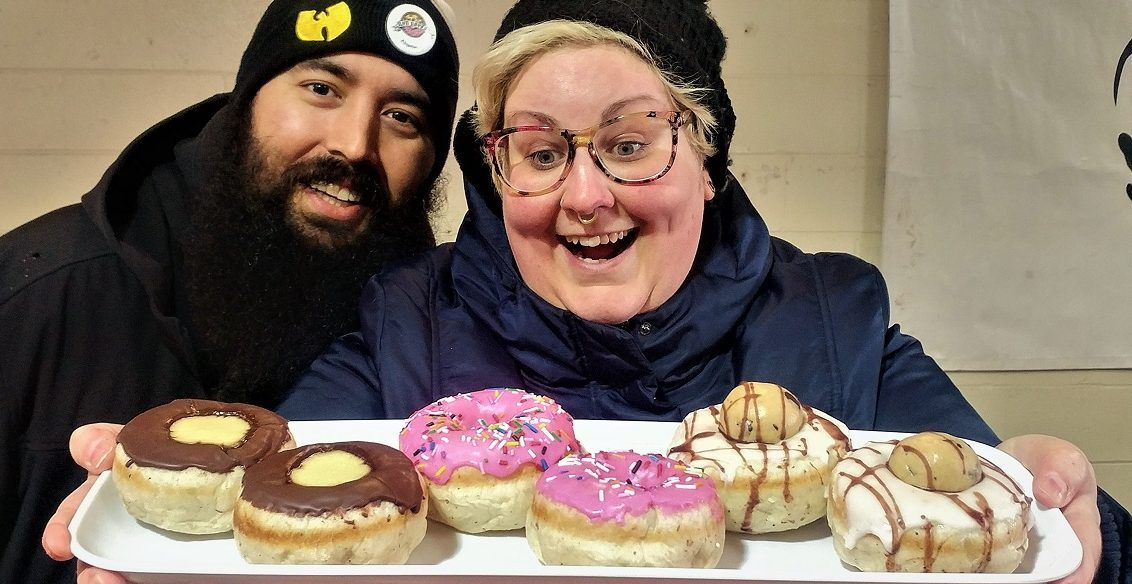Head shot of woman and man, with the woman holding a tray of 6 donuts.