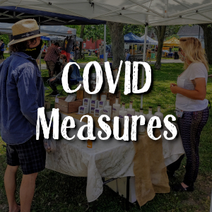 """Faded image of market vendor and shopper on a sunny day. They demonstrate appropriate distancing measures. Superimposed text reads """"covid measures"""""""